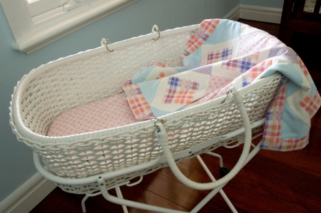 white basinet with handmade bedding