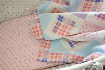 pink, orange, blue and purple basinet bedding